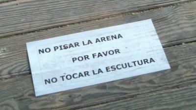 No pisar la arena. No tocar la escultura