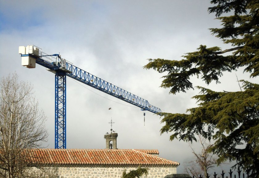 construction crane and storks over church tower