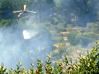 helicopter dropping water on a wild fire