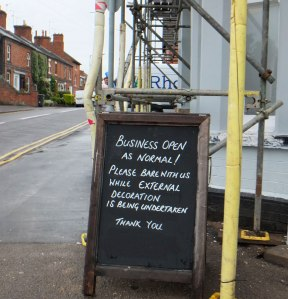 Sign: Business open as normal. Please bare with us while external decoration is being undertaken