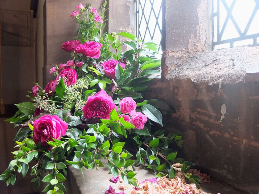 flower arrangement of pink/red roses in old church