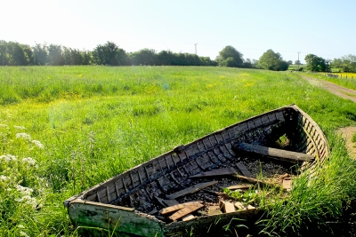 old wooden rowing boat in a field