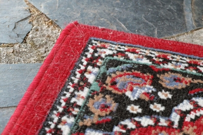 corner of old red-edged rug