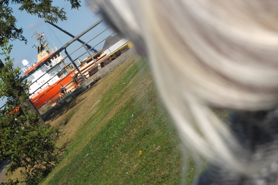 Green grass, orange & white boat, blue sky, granny hair in foreground.