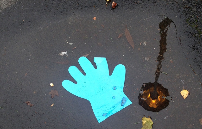 blue plastic glove  in puddle
