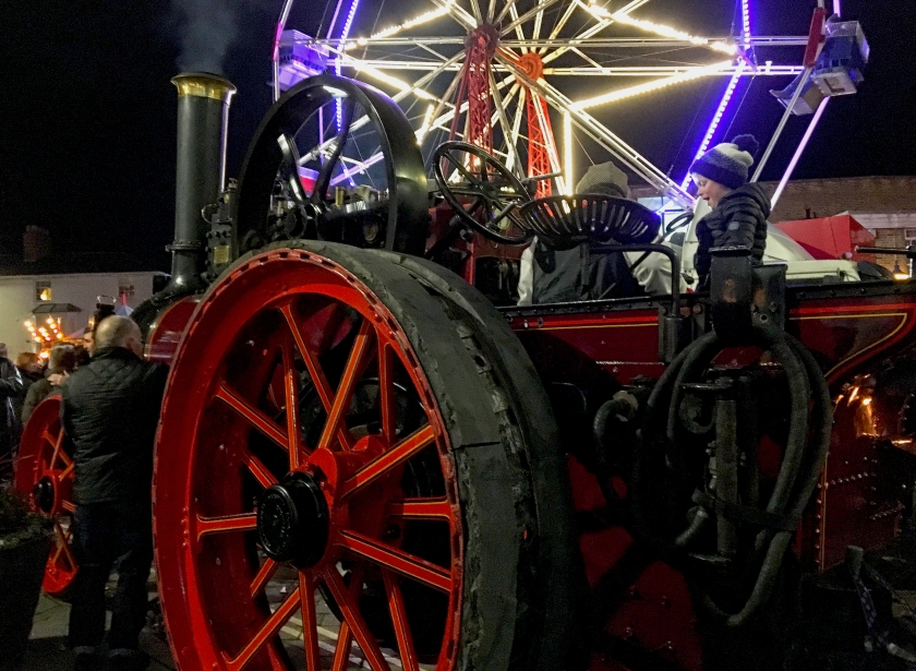 old steam engine with modern ferris wheel behind
