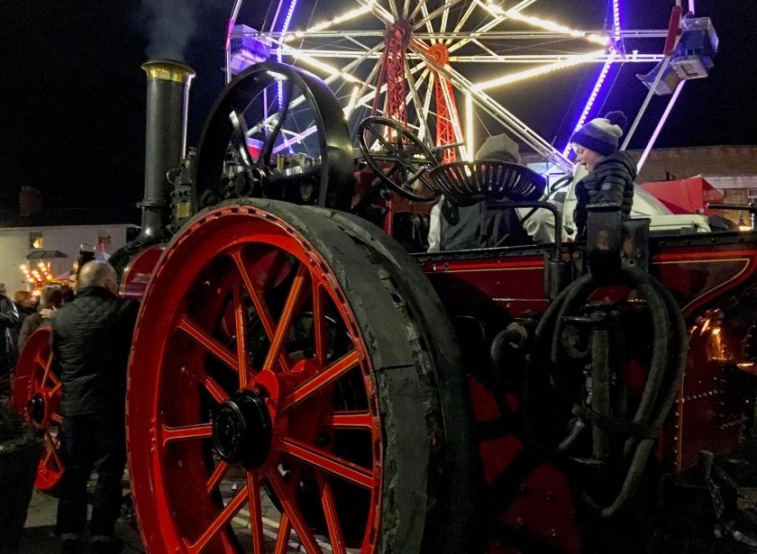 old steam engine with modern ferris wheel behind