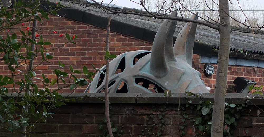 iron horse sculpture ears seen above wall
