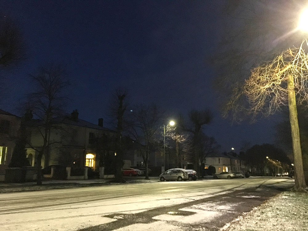 sprinkling of snow on wide urban road before sunrise