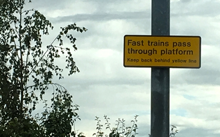 Railway sign: fast trains pass through station
