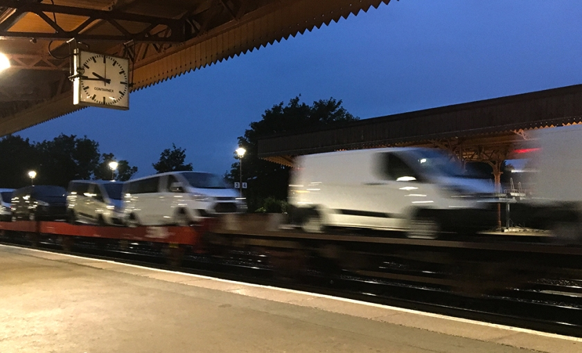 White vans being transported by rail