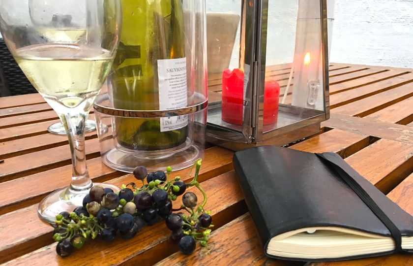 grapes, notebook, white wine half-full glasses on wooden outdoor table