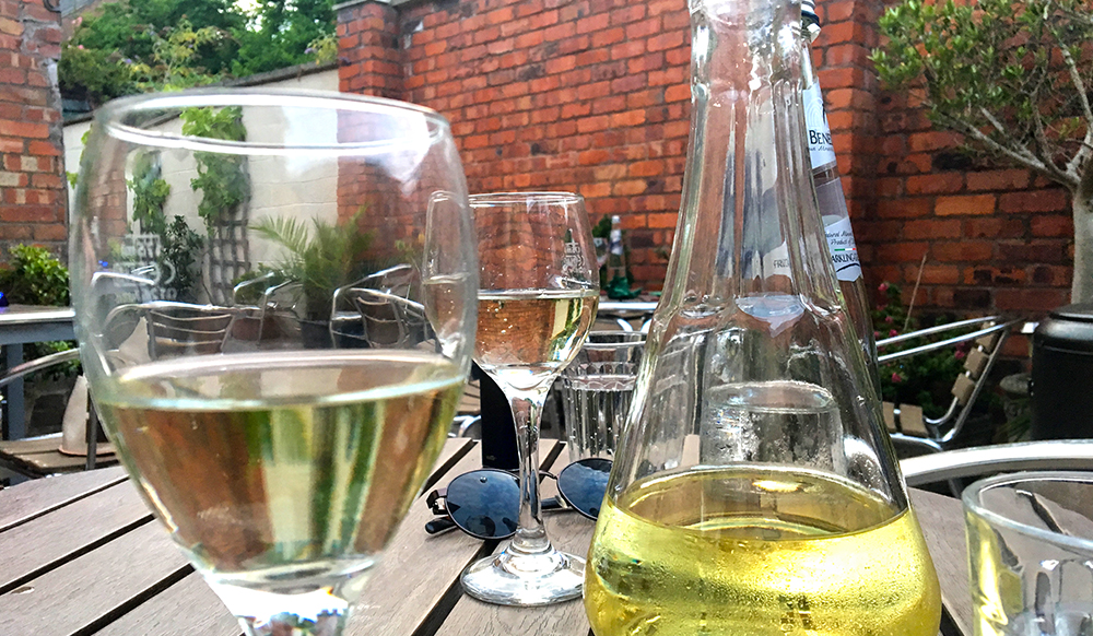 white wine carafe and half-full glasses on wooden outdoor table