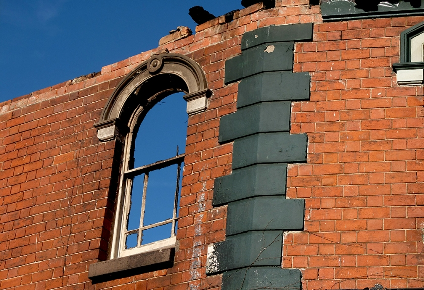 blue sky seen through arched window with no glass in burned out building