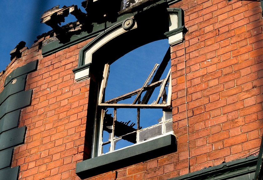blue sky and building ruins seen through window with no glass in burned out building