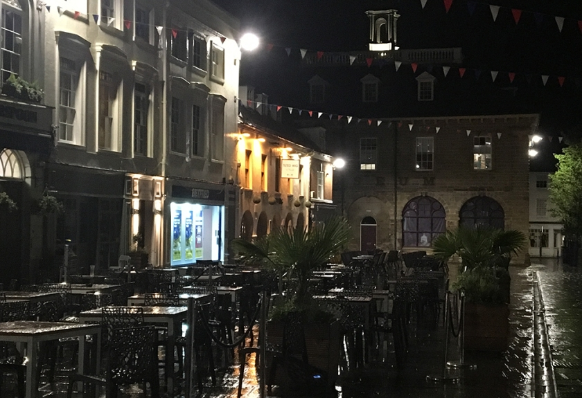 pub tables & chairs; market square; wet night