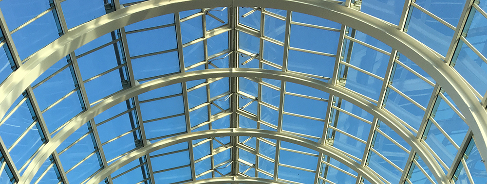 blue sky through shopping mall glass ceiling