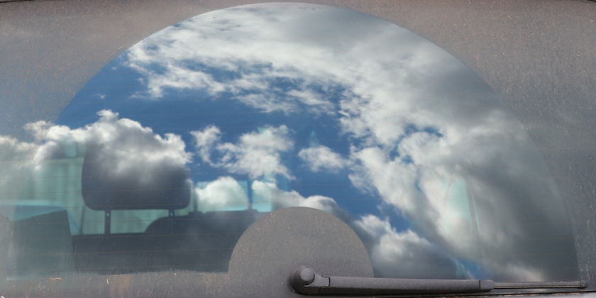 clouds reflected in car rear window