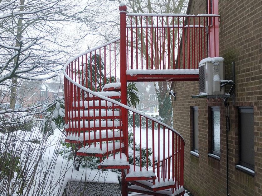 red spiral fire escape in the snow