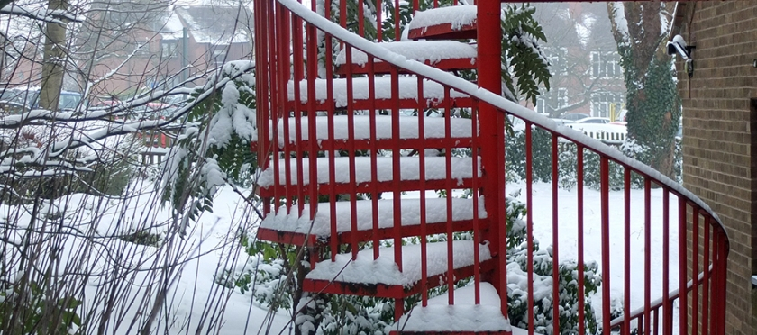 red metal spiral fire escape  with snow