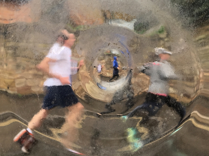 marathon runners seen through distorting window