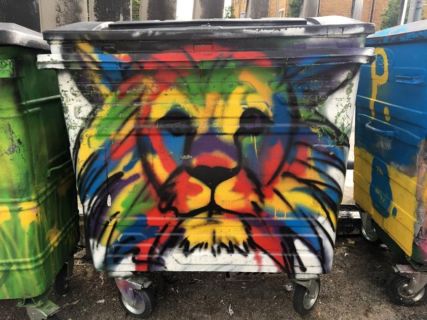 multicoloured lion graffiti on community bin