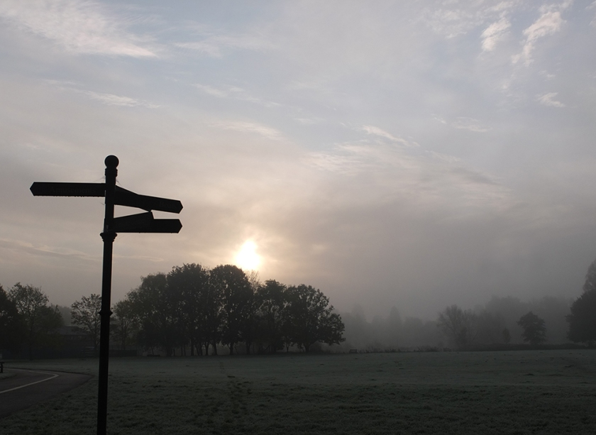Misty morning. Sun coming up. Signpost sulhouetted