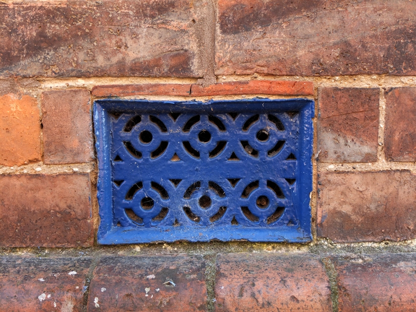 blue metal grating. Red brick wall