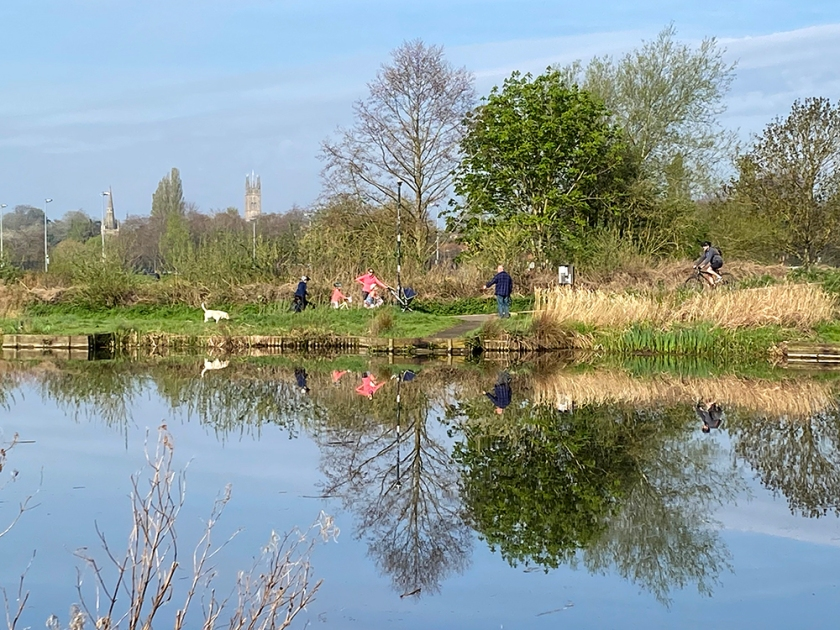 Group of people reflected in pond