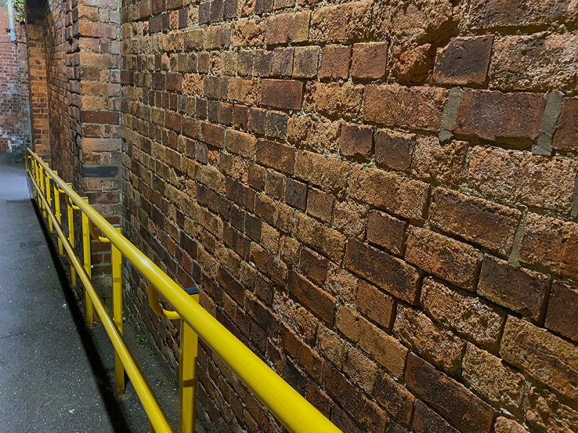 Station ramp: red brick wall, yellow hand rail.