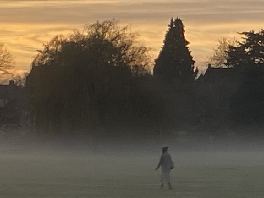 figure crossing misty field at sunrise