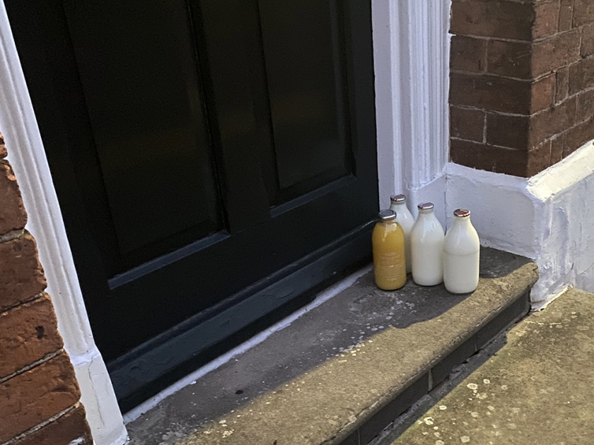 milk and orange juice in bottles on a doorstep