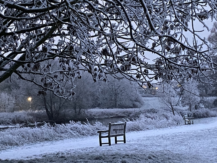 snowy bench on river bank