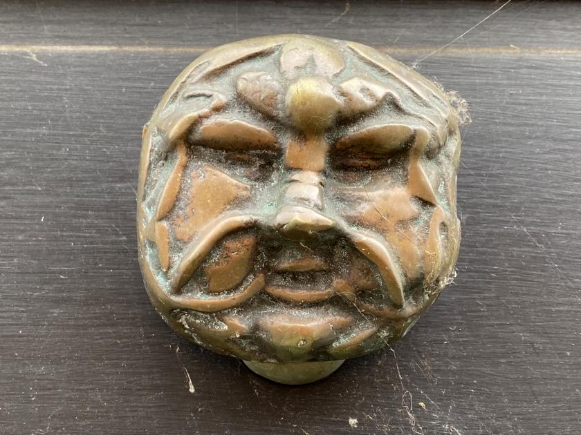 Old metal door knob with green man face